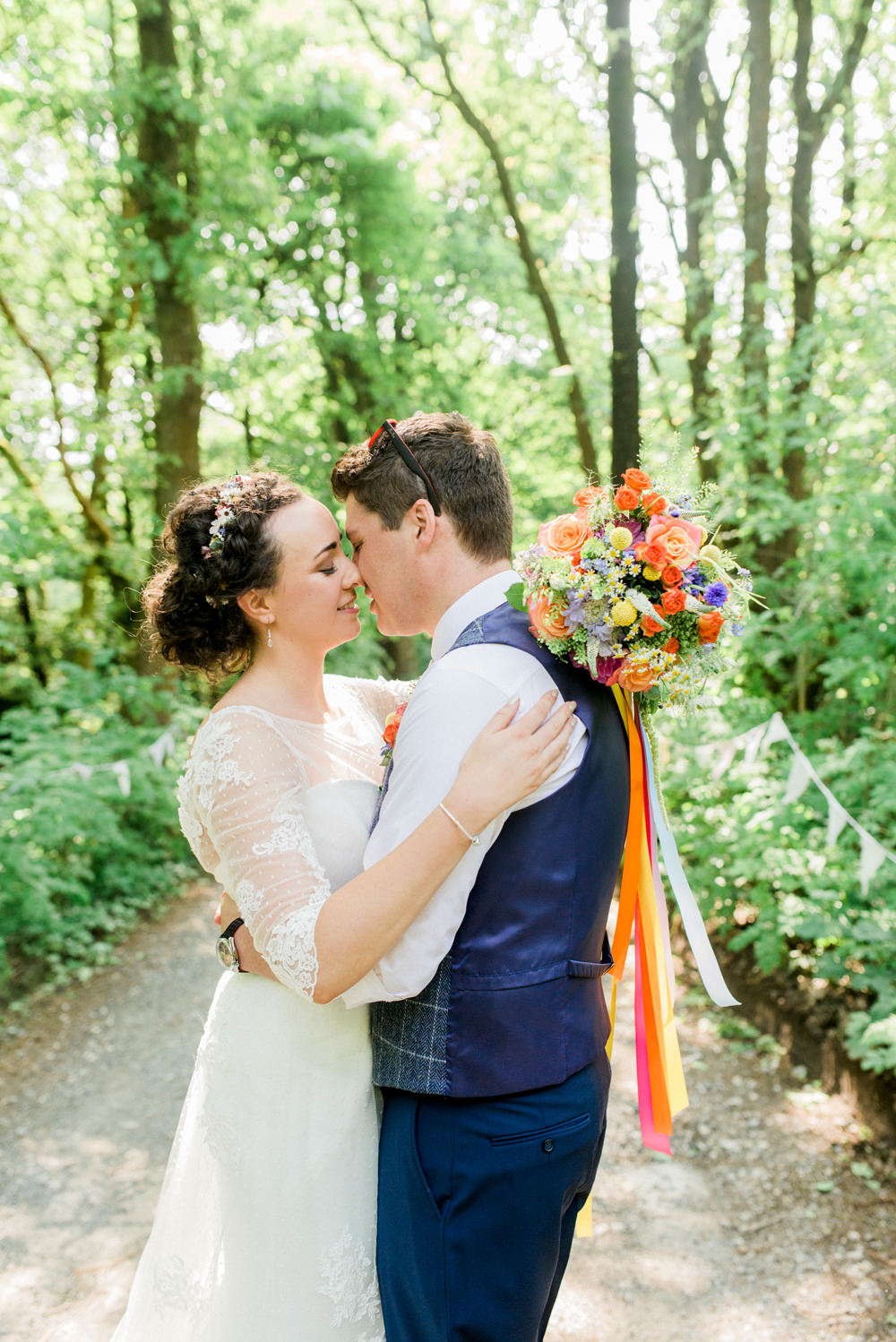 Bride Bridal Strapless Sweetheart Neckline Lace Jacket Sleeves Waistcoat Groom Blue Multicoloured Bouquet Ribbon Spring Cottage Rivington Wedding Emma B Photography