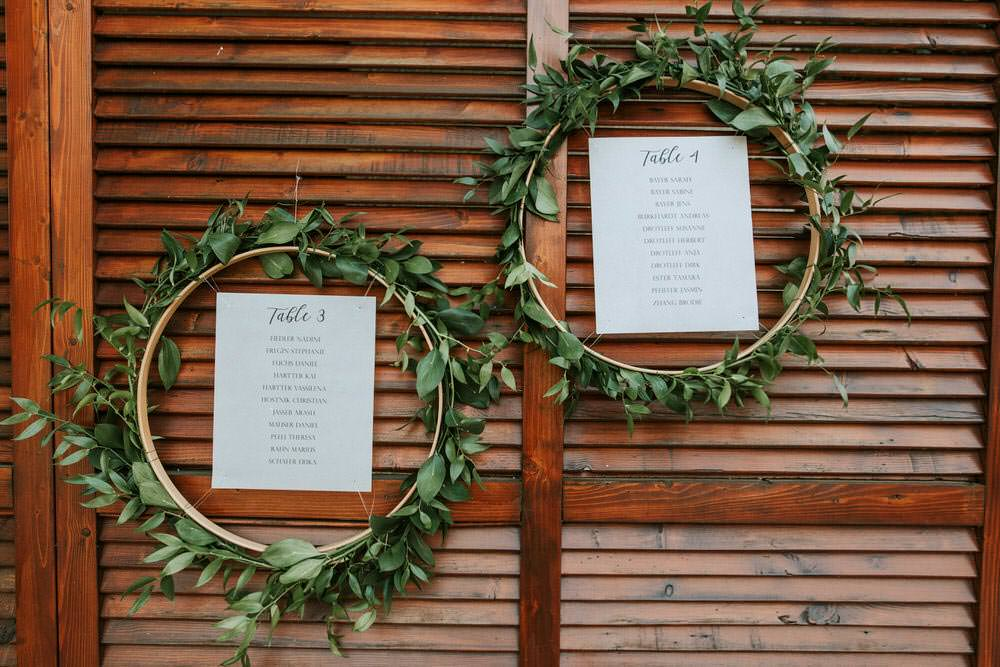 Seating Plan Table Chart Table Botanical Greenery Foliage Wreath Hoop Backdrop Flowers Bohemian Beach Greece Destination Wedding Lighthouse Photography