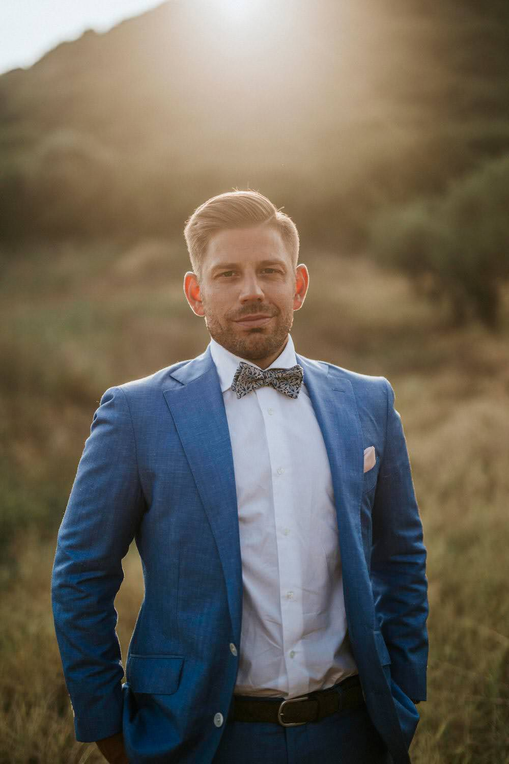 Groom Blue Suit Bow Tie Bohemian Beach Greece Destination Wedding Lighthouse Photography