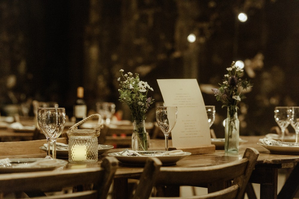 Long Wooden Tables Chairs Flowers Bottles Brunel Museum Wedding Olivia and Dan Photography