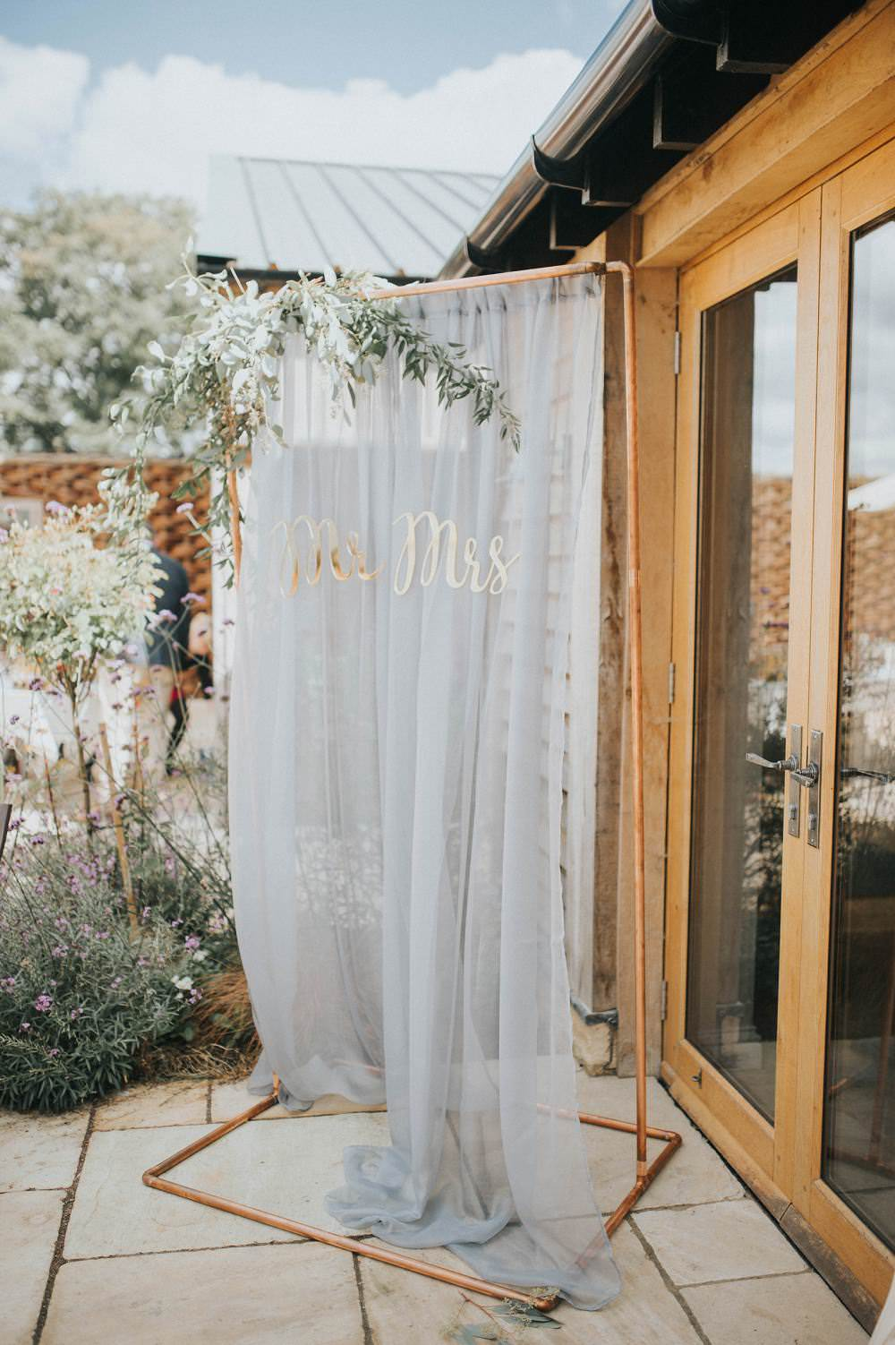 Backdrop Sign Photo Booth Copper Pipe Metal Silk Fabric Grey Mr Mrs Gold Letters Foliage Eucalyptus Boho Greenery Barn Wedding Kerry Diamond Photography