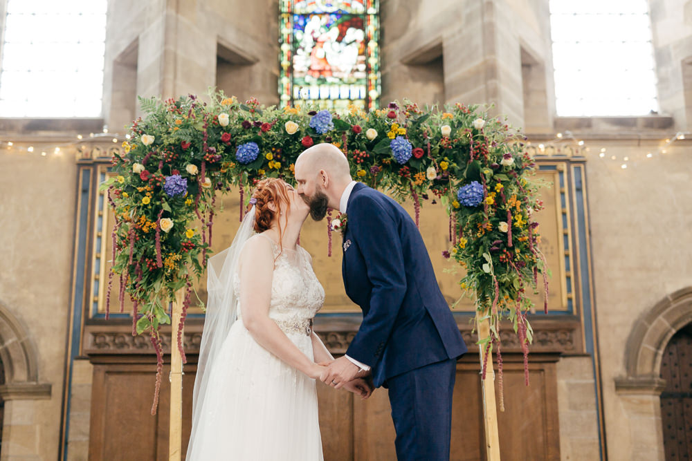 Bride Bridal Sweetheart Overlay Dress Navy Suit Groom Tweed Waistcoat Veil Multicoloured Floral Ceremony Arch Left Bank Leeds Wedding Amber Marie Photography