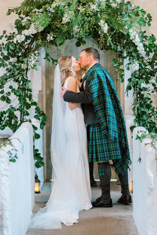 Bride Bridal Deep V Plunge Neckline Dress Sleeveless Slim Fit Ogilvie Tartan Kilt Groom Veil Foliage Arch Ceremony Tin Shed Knockraich Farm Wedding The Gibsons Photography