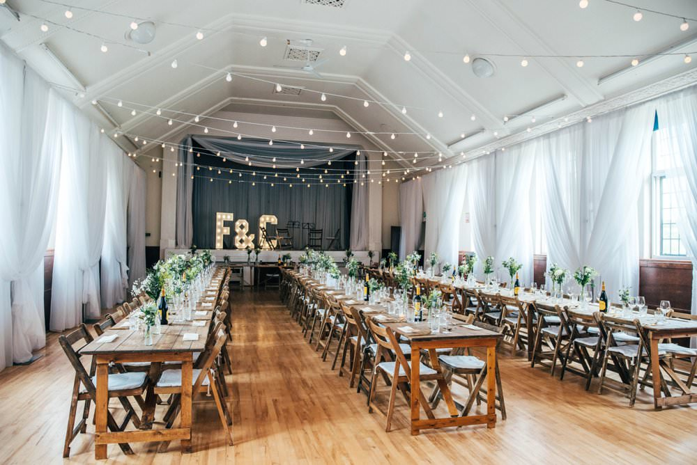 Festoon Lights Trestle Tables Long Wooden Chairs Chichester Hall Wedding Three Flowers Photography