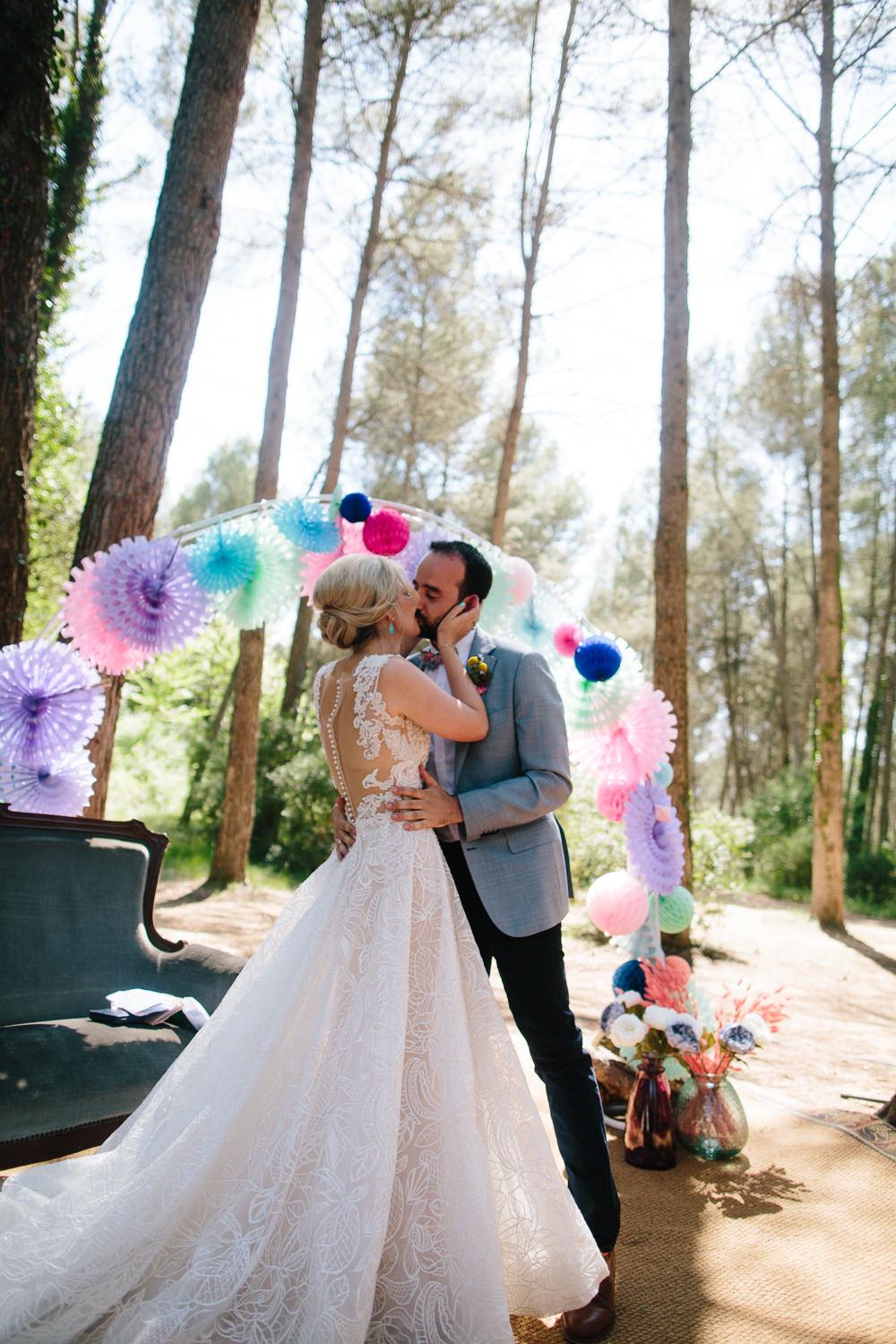 Bride Bridal Lace Strappy Sleeveless Embellished Dress Gown Mismatched Bow Tie Groom Bright Coloured Pin Wheel Paper Lantern Arch Forest Spain Destination Wedding Dan Hough Photography