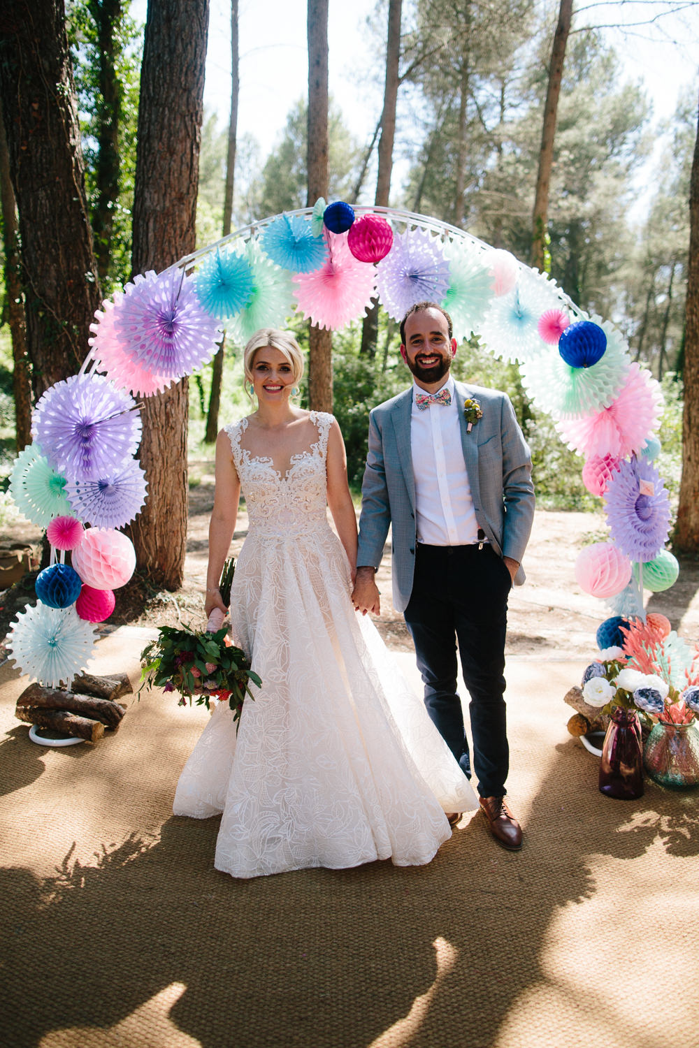 Bride Bridal Lace Strappy Sleeveless Embellished Dress Gown Mismatched Bow Tie Groom Pin Wheel Paper Lantern Arch Forest Spain Destination Wedding Dan Hough Photography