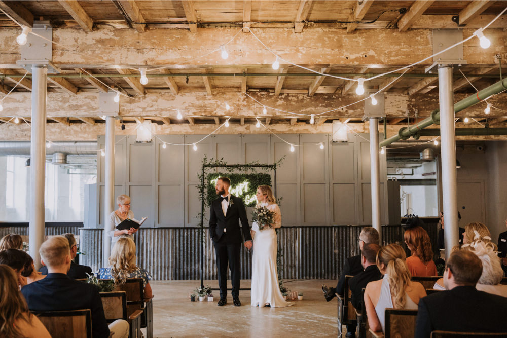 Industrial Venue Ceremony Decor Festoon Lights Backdrop Neon Sign Frame Arch Greenery Foliage Holmes Mill Wedding Siobhan Amy Photography