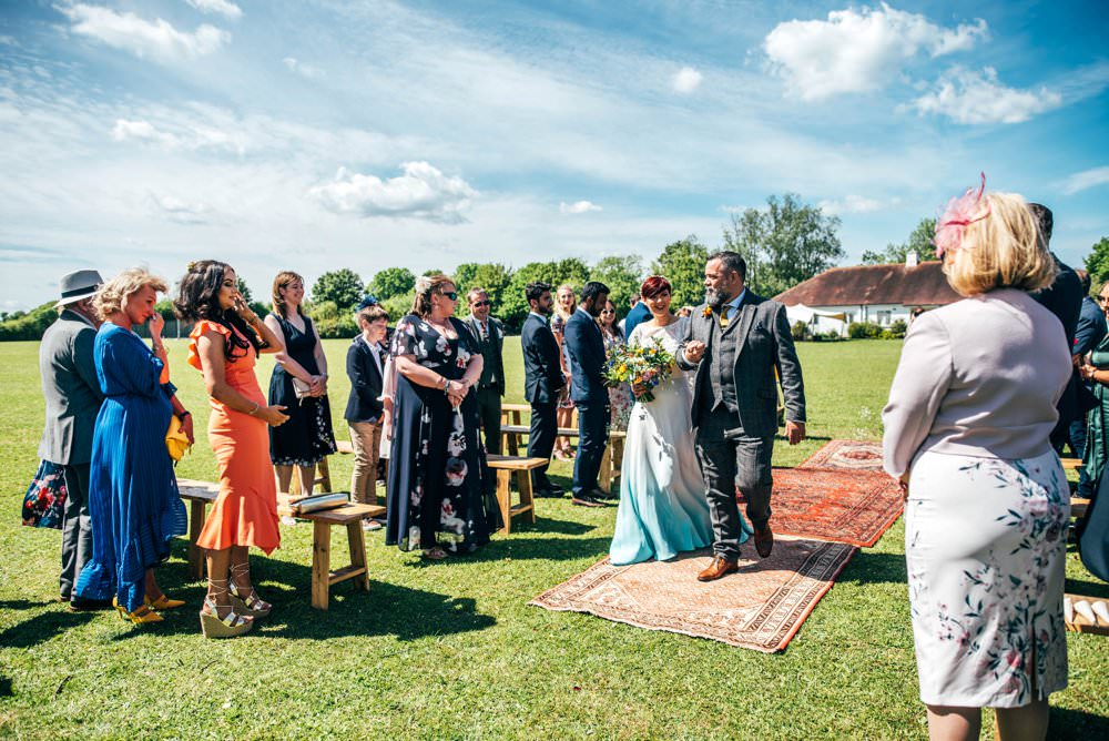 Ceremony Village Hall Essex Persian Rug Aisle Frame Arch Backdrop Greenery Foliage Flowers Benches Outdoor DIY Wedding Three Flowers Photography