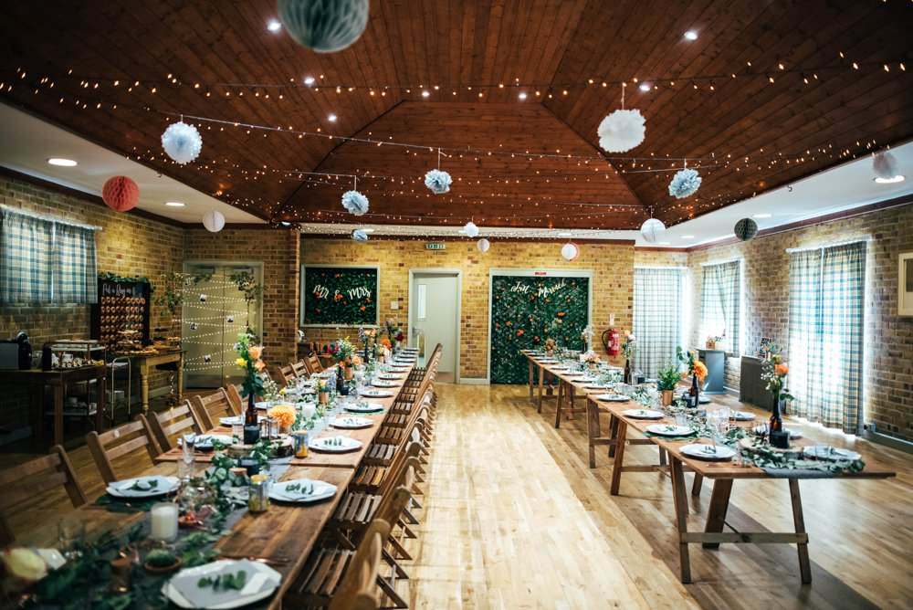 Long Rustic Wooden Tables Folding Chairs Pom Poms Village Hall Fairy Lights Outdoor DIY Wedding Three Flowers Photography