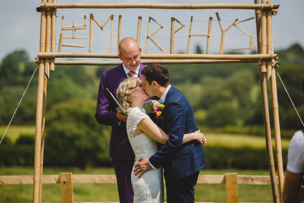 Bride Bridal High Neck Cap Sleeve Lace Fitted Dress Gown Bow Tie Waistcoat Groom Wes Anderson Camp Sign Backdrop East Keswick Village Hall Wedding James & Lianne Wedding Photography
