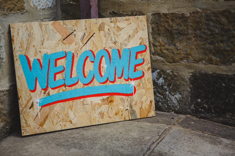 Welcome Painted Sign Wood East Keswick Village Hall Wedding James & Lianne Wedding Photography