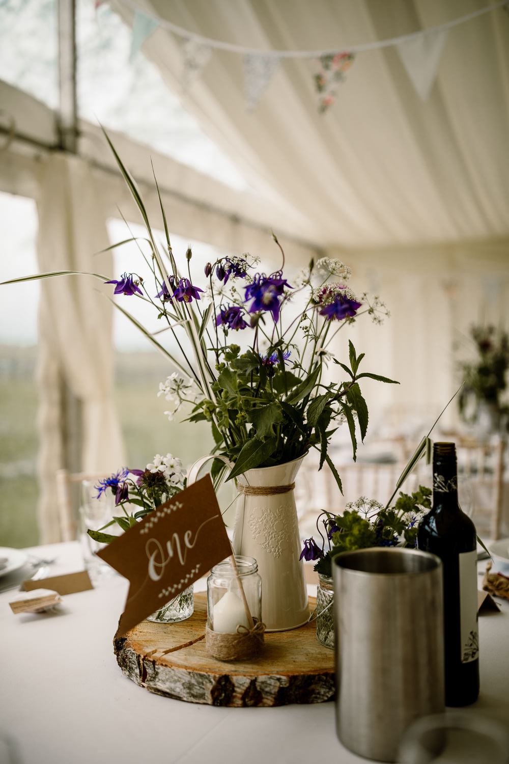 Centrepiece Table Decor Decorations Log Slice Jug Flowers Purple Pennant Flag Table Name Candle Yorkshire Barn Wedding Hayley Baxter Photography