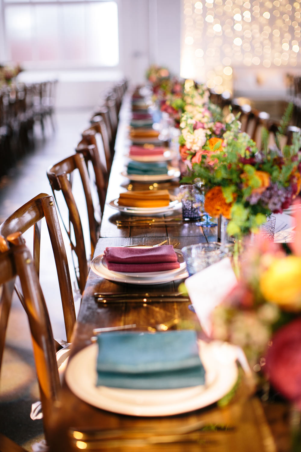 Long Tables Wooden Cross Back Chairs Colourful Lanterns Flowers Napkins Bridal Jumpsuit Wedding Emily Jarrett Photography