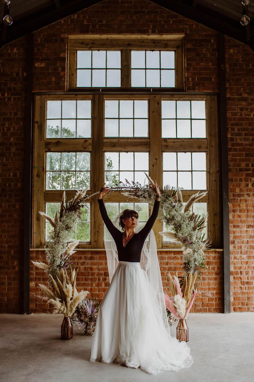 Bride Bridal Ballet Top Shirt Shoes Moon Gate Flower Arch Pampas Grass Backdrop Ceremony Venue Giraffe Shed Wedding When Charlie Met Hannah