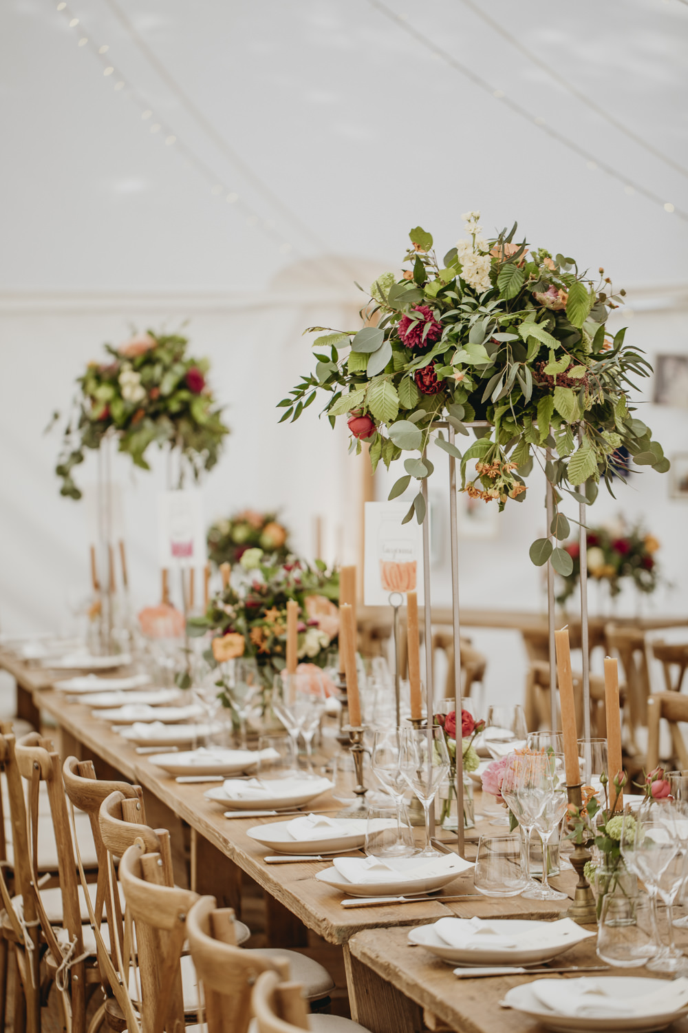 Long Wooden Tables Cross Back Chairs Tall Flowers Arrangements Centrepiece Greenery Foliage Kent Marquee Wedding Lily Bungay and Co