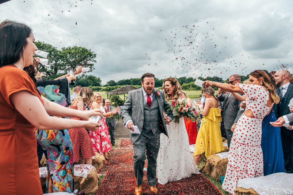 Confetti Outdoor Ceremony Persian Rugs Hay Bales Pink Red Wedding Three Flowers Photography