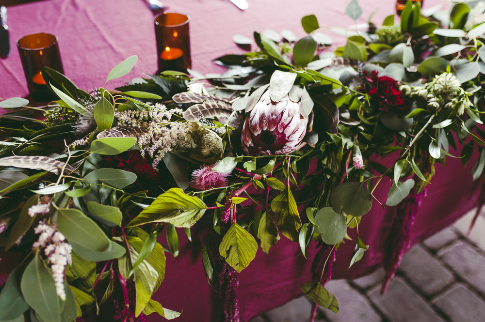 Top Table Red Burgundy Table Cloths Greeenery Foliage Protea Flowers Kingshill Barn Wedding Sandra Reddin Photography