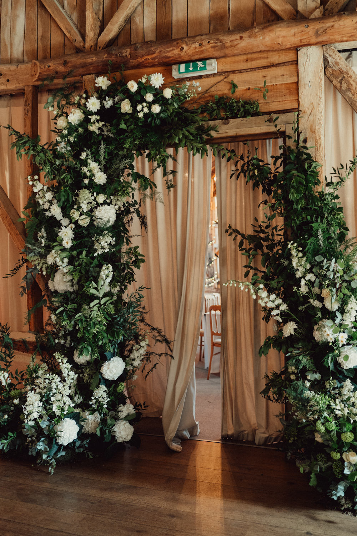 Flower Arch Installation Greenery Foliage White Flowers Backdrop Countryside Barn Wedding Emily & Steve Photography