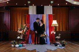 Village Hall Wedding Emily + Katy Photography Ceremony Backdrop Drapes Fabric Monochrome Rug Festoon Lights Flowers